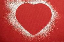 Forma de corazón rojo delineado en azúcar glaseado - foto de stock