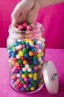 Vista recortada de la mano tomando bolas de goma de mascar de colores fuera del frasco - foto de stock