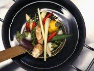 Verdure per minestra tailandese nel wok nero sulla superficie di legno — Foto stock