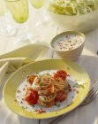 Grilled scallops with tomatoes on yellow plate over table — Stock Photo