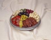 Prato com tomates secos ao sol, pepperoncini, azeitonas e cogumelos sobre pano — Fotografia de Stock