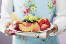 Frau serviert Teller mit frischem Obst — Stockfoto