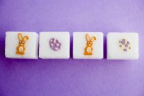 Closeup top view of sugar cubes with Easter decorations in a row — Stock Photo