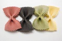 Pasta farfalle coloreada en fila - foto de stock