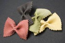 Piezas de pasta farfalle de colores - foto de stock