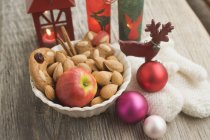 Christmas decoration with apple and mittens — Stock Photo