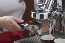 Cropped view of woman holding filter holder of Espresso machine with coffee powder — Stock Photo