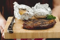 Grilled steak with baked potatoes — Stock Photo
