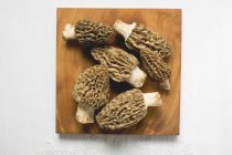 Several morels on wooden board — Stock Photo