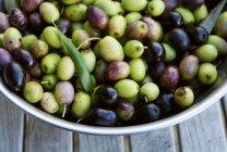 Aceitunas verdes y negras en tazón de fuente - foto de stock