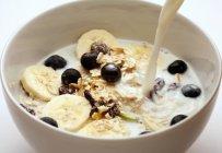 Milch in Müsli mit Bananen gießen — Stockfoto