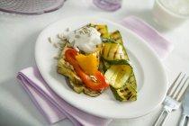 Овощи гриль с crme frache и подсолнечника на белом фоне полотенце с вилкой — стоковое фото