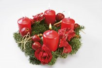 Une couronne de l'Avent avec des bougies rouges sur une surface blanche — Photo de stock