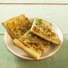 Tre pezzi di crostata di cipolla su un piatto sulla superficie verde — Foto stock