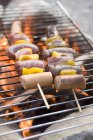 Sausages and pepper kebabs on barbecue — Stock Photo