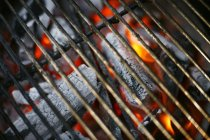 Closeup view of glowing coals under barbecue rack — Stock Photo