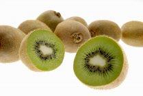 Kiwi fruits, one halved — Stock Photo