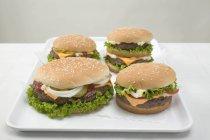 Four cheeseburgers on tray — Stock Photo