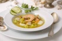 Vista del primo piano di un piatto di zuppa di pesce con fette della calce e gamberetti — Foto stock