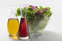 Closeup view of oil and vinegar in carafes in front of salad bowl — Stock Photo