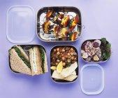 Insalate, spiedini di verdure e panini in scatole di pranzo sulla superficie viola — Foto stock