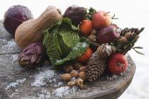 Vista de cerca de manzanas aún con verduras, frutos secos y conos en mesa de madera - foto de stock