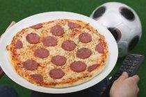 Mano maschio che tiene il piatto con la pizza — Foto stock