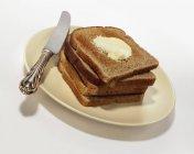 Vista de cerca de apilado tostadas con mantequilla en plato con cuchillo - foto de stock