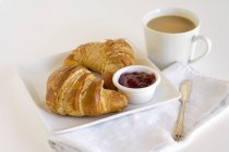 Croissants with jelly on plate — Stock Photo