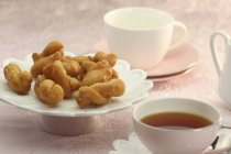 Koeksisters  with tea on the plate — Stock Photo