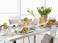 Breakfast with orange juice and croissants — Stock Photo