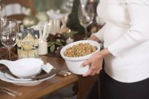 Woman placing dish — Stock Photo
