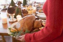 Woman serving roast turkey — Stock Photo