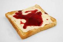Vista del primo piano di toast imburrati con marmellata su superficie bianca — Foto stock