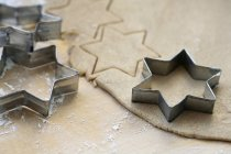 Closeup view of biscuit dough with star-shaped cutters — Stock Photo