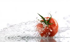 Red tomato surrounded with water — Stock Photo