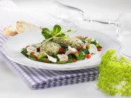Спаржа gnocci на салате ягненка с грибами и полосками ветчины на белой тарелке над полотенцем — стоковое фото