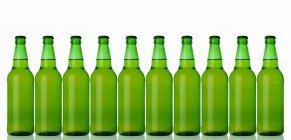 De pé em uma fileira de garrafas verdes — Fotografia de Stock