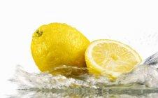 Lemons with splashing water — Stock Photo