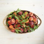Organic peaches in basket — Stock Photo