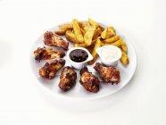 Alette di pollo barbecue con spicchi di patate — Foto stock