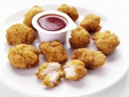 Vista de closeup de nuggets de frango com molho no prato branco — Fotografia de Stock
