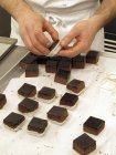 Primo piano ritagliata vista di persona aggiunta di cubetti di cioccolato ai casi di pralina — Foto stock