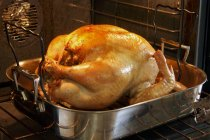 Closeup view of whole turkey in a roasting pan in the oven — Stock Photo