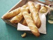 Baguettes sur plateau en bois — Photo de stock