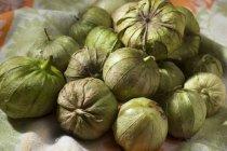 Many Fresh Tomatillos laying on textile towel — Stock Photo