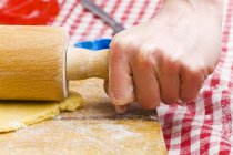 Closeup view of person rolling out biscuit dough — Stock Photo