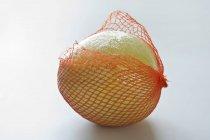 Pomelo maturo fresco in rete — Foto stock