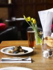 Elevated view of lunch with beer and flowers on restaurant table — Stock Photo