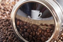 Cup and coffee beans heap reflected in metal tin surface — Stock Photo
